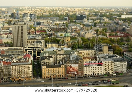 WARSAW, POLAND - MAY 1, 2016. View over Warsaw at dusk, with Church of St. Barbara, residential and commercial buildings,  street traffic, commercial properties and people. #579729328