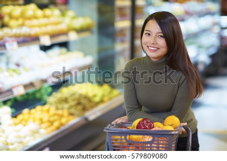 One Young Chinese Woman Shopping in the Supermarket #579809080