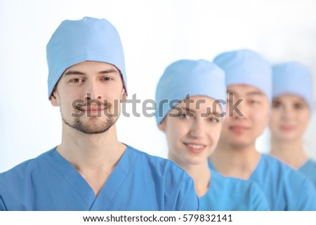 Handsome young doctor with colleagues in clinic #579832141