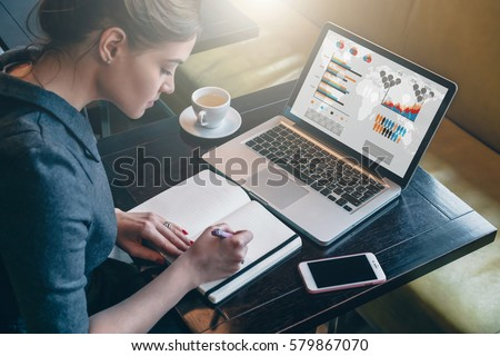 Side view. Young business woman sitting at table and taking notes in notebook.On table is laptop, smartphone and cup of coffee.On computer screen graphics and charts. Student learning online. Blogger. Royalty-Free Stock Photo #579867070