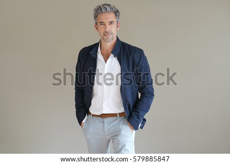 Handsome mature man standing on grey background, isolated Royalty-Free Stock Photo #579885847