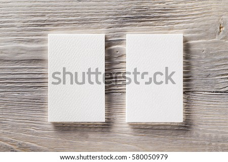 Closeup mockup of two blank vertical business cards at light natural wooden background.