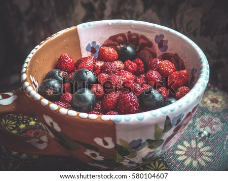 Freshly sweet strawberries and currants in a bright ceramic cup on a vintage table of decoupage. #580104607
