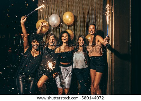 Shot best friends celebrating new year's eve holding sparklers in a party. Group of women having party at nightclub. #580144072