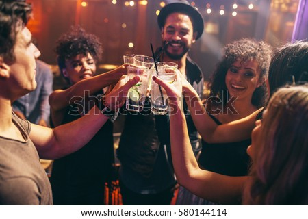 Group of friends having drinks at the night club party. Young people enjoying at a bar toasting cocktails. Royalty-Free Stock Photo #580144114