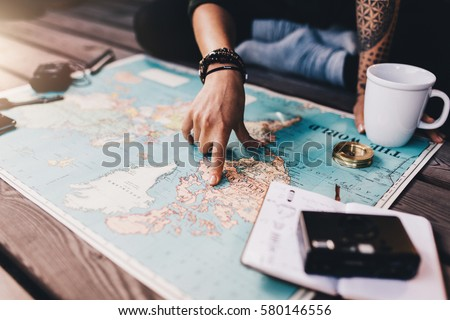 Tourist planning vacation with the help of world map with other travel accessories around. Young woman pointing at North America on the world map. #580146556