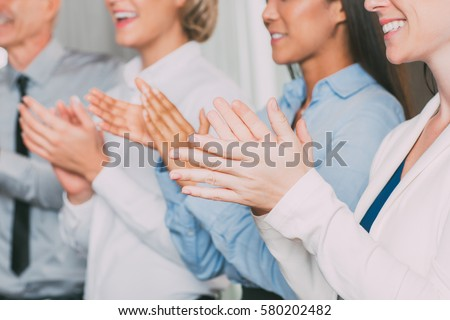 Closeup of Four Smiling Business People Applauding #580202482