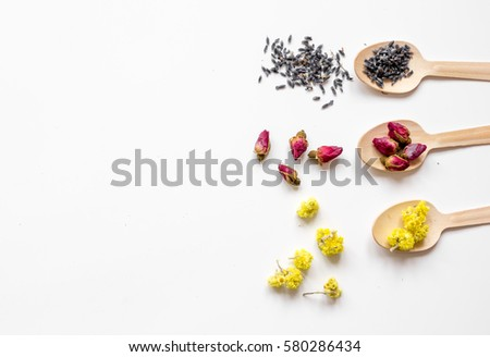 Virious herbs in wooden spoons on white table top view mockup #580286434
