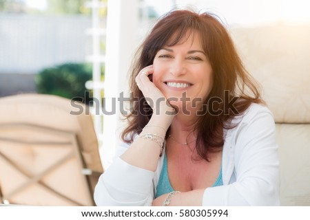 Attractive Middle Aged Woman Smiles On The Patio. Royalty-Free Stock Photo #580305994