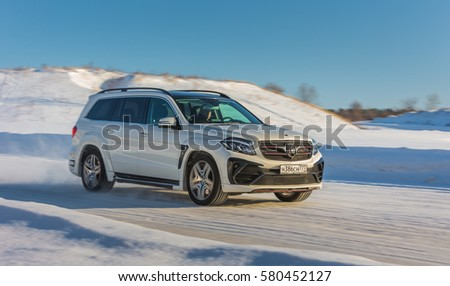 Russia, Togliatti - DECEMBER 22, 2016: Snow test drive of Mercedes GL and GLS with tuning kit Black Crystal of LARTE Design Tuning Company. Luxury SUV in deep snow and various weather conditions #580452127