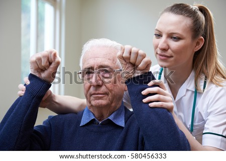 Nurse Assessing Stroke Victim By Raising Arms #580456333