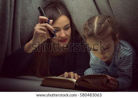 Little girl and her mother reading fairy tales book under the covers at the evening with lantern. Cute kid playing before going to sleep, image toned. Home family leisure. #580483063