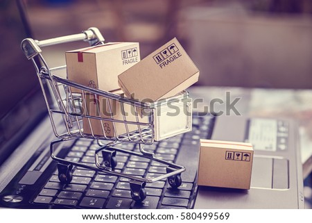 Boxes in a trolley on a laptop keyboard. Ideas about online shopping, online shopping is a form of electronic commerce that allows consumers to directly buy goods from a seller over the internet. Royalty-Free Stock Photo #580499569