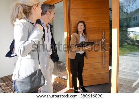 Real estate agent inviting couple to enter house for visit                      Royalty-Free Stock Photo #580616890