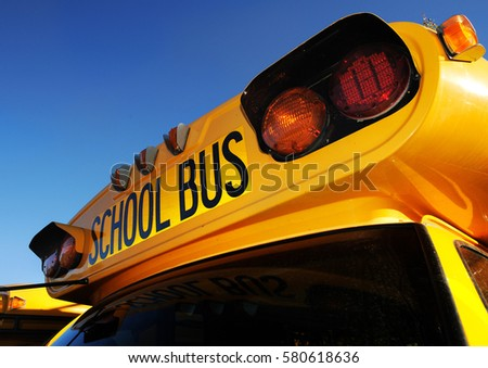 Front part of yellow school bus children educational transport with signs in the parking lot waiting to be in service. Close up photo of school bus in sunny day with clean blue background. #580618636