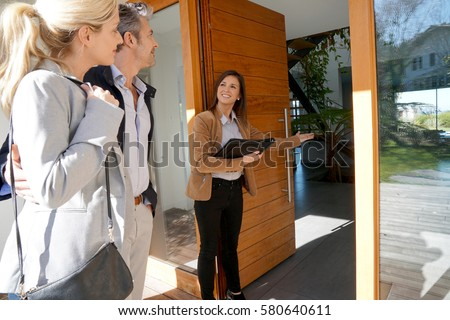 Real estate agent inviting couple to enter house for visit                      #580640611
