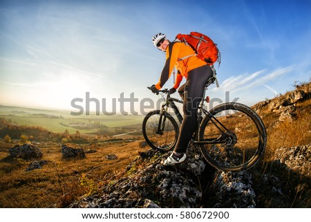 Cyclist in helmet and glasses on mountain bike stands on the precipice of hill under blue sky and sun. Wide angle view #580672900