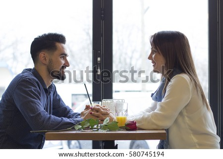 Beautiful young couple sitting at the table in cafe #580745194