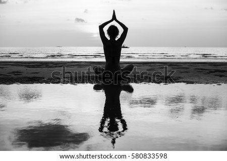 Yoga silhouette. Woman doing meditation near the ocean beach. Black and white photo. #580833598