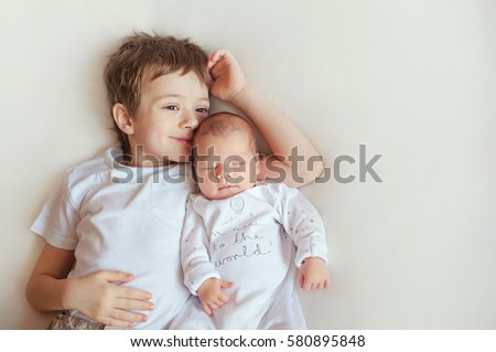 Little brother hugging her newborn baby. Toddler kid meeting new sibling. Cute boy and new born baby girl relax in a white bedroom. Family with children at home. Love, trust and tenderness