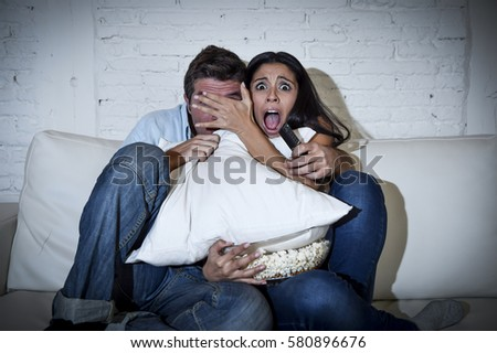 young happy attractive couple having fun at home enjoying watching television horror movie show or thriller film covering eyes together scared in shock at home sofa couch terrified #580896676