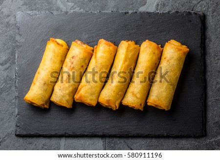 Fried spring rolls on black slate plate on grey stone slate background. Top view #580911196