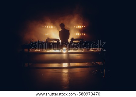 DJ set on a stage, silhouette in a warm backlight with two turntables Royalty-Free Stock Photo #580970470