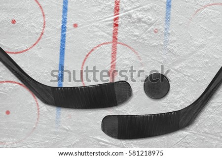 Two hockey sticks, puck and a hockey field with marking. Concept, detail, hockey