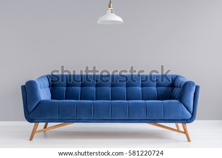 Grey interior with stylish upholstered blue sofa and lamp #581220724
