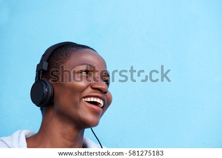Close up portrait of smiling african woman listening to music with headphones #581275183