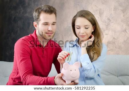 Young couple saves into piggybank. savings money couple piggybank home budget marriage cost concept #581292235
