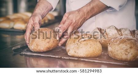 Baker checking freshly baked bread in the kitchen #581294983