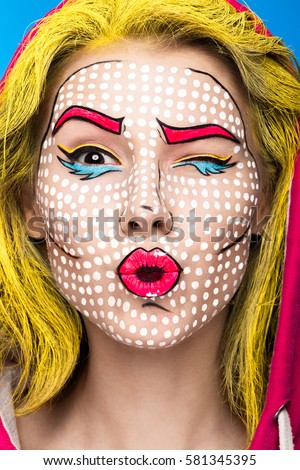 Photo of surprised young woman with professional comic pop art make-up and design. Creative beauty style. Photos shot in studio