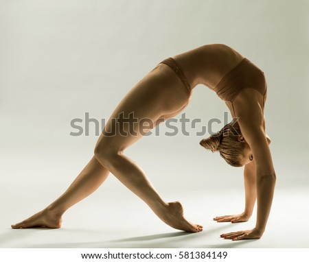 Gold skin woman staying in back-bend studio shot #581384149