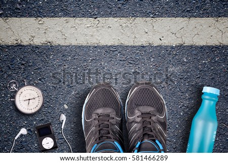 Men Running shoes and run equipment on asphalt.  Running training on hard surfaces. Runner Equipment stopwatch and music player. The necessary water bottle. Asphalt on the background. Time to running. #581466289