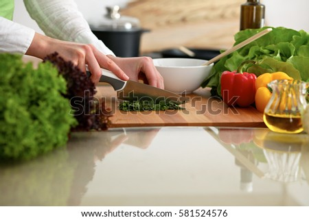 Closeup of human hands cooking vegetables salad in kitchen on the glass table with reflection. Healthy meal and vegetarian concept #581524576