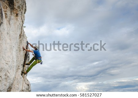 Young male climber hanging by a cliff #581527027