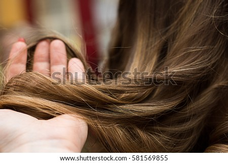 Close up view of hairdresser hand holding strand of hair preparing to cutting and dyeing hair. #581569855