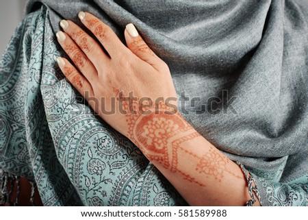 Woman hand with henna mehendi on indian shawl pashmina closeup.