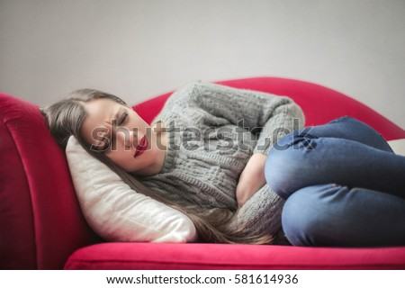 Young girl with stomach pain lying on the sofa #581614936