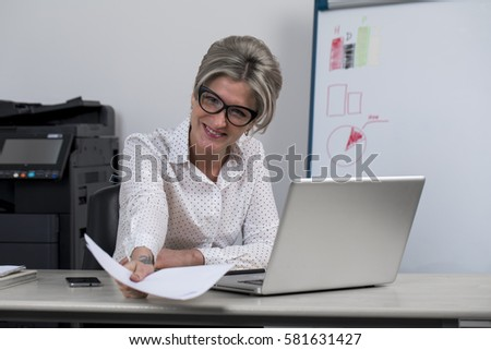 Secretary in the office. Portrait of a beautiful young woman in a white blouse and black skirt on office background #581631427