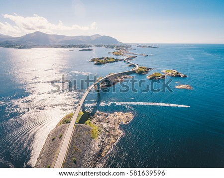 "Aerial drone shot of the world famous Atlantic Road is known as ""The Road in the Ocean"" in Norway. This fantastic and spectacular road and bridge is a very popular tourist attraction. Royalty-Free Stock Photo #581639596"
