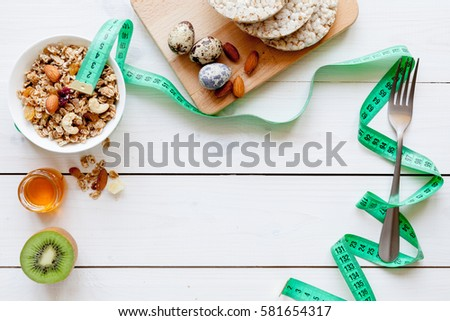 Concept diet - healthy food with muesli, eggs, honey, kiwi and cereals #581654317