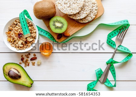 Concept diet - healthy food with muesli, honey, kiwi and cereals #581654353