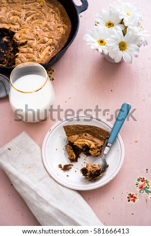 Overhead of a peanut butter swirl brownie slice with blue spoon and baked brownies in a cast iron skillet with a cold glass of milk, vase of white daisies and beige linen on a pink wooden surface. #581666413