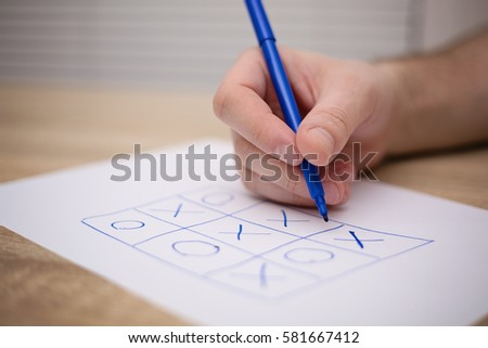 male adult hand holding blue pen above a paper with a tic-tac-toe game #581667412