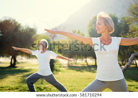 Yoga at park. Senior family couple exercising outdoors. Concept of healthy lifestyle. Royalty-Free Stock Photo #581710294