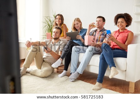 friendship, people, technology and entertainment concept - happy friends with tablet pc computer and smartphone eating popcorn, drinking beer or cider and watching tv at home #581725183