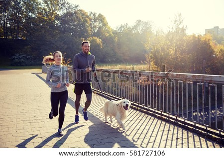 fitness, sport, people and jogging concept - happy couple with dog running outdoors #581727106
