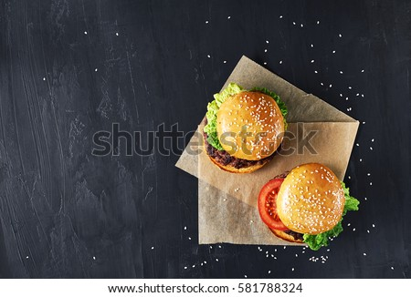 Craft beef burgers with vegetables. Flat lay on black textured background with sesame seeds. #581788324
